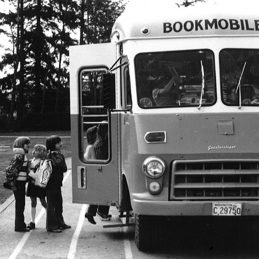 Photo of Bookmobile with small children lined up to enter.