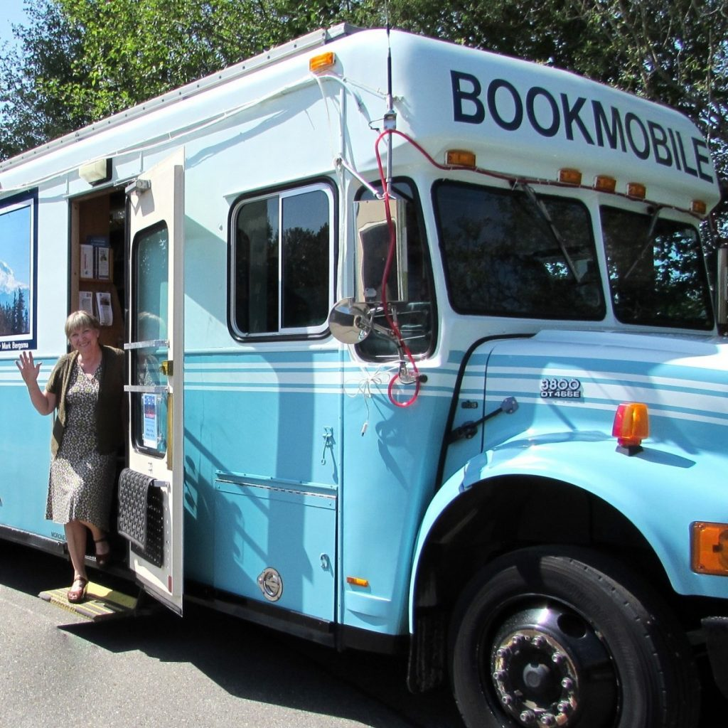 Photo of bookmobile with woman waving from doorway.