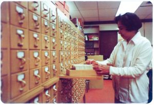 Old photo of librarian at library card catalog