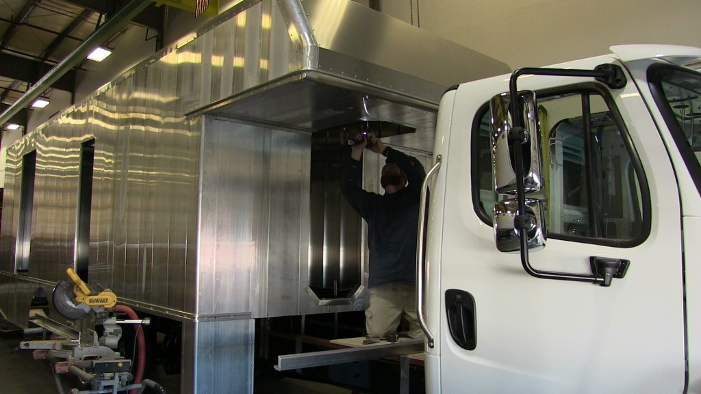 TriVan mechanic working on Bookmobile entryway