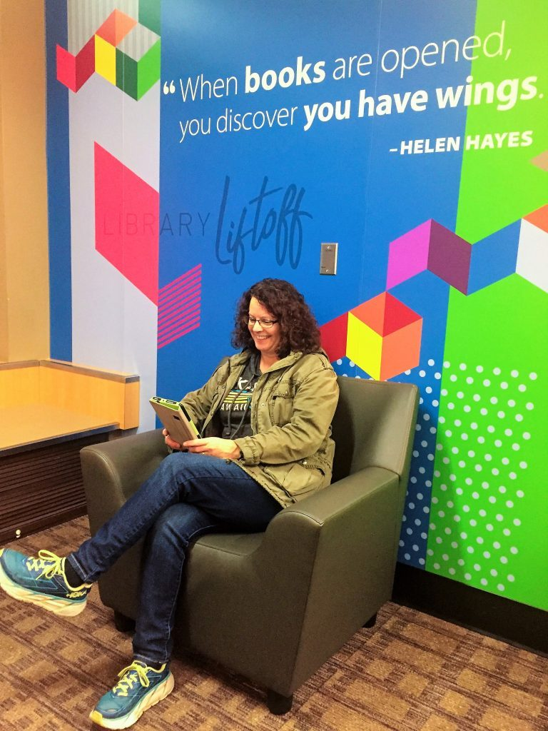 photo of woman sitting in chair reading a book at the Bellingham International Airport