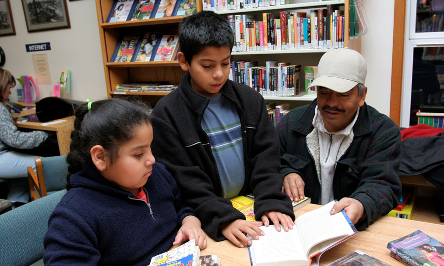 Photo of man with two children reading together