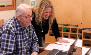 Photograph of staff member helping older man on computer