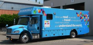 "Photo of new bookmobile. Quotation painted on side: ""When we read, we are able to travel to many places, meet many people, and understand the world."" Nelson Mandela"