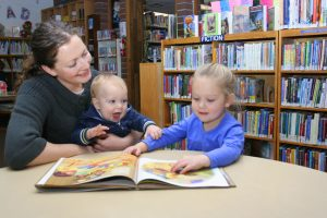 Photo of mom with two children looking at a book