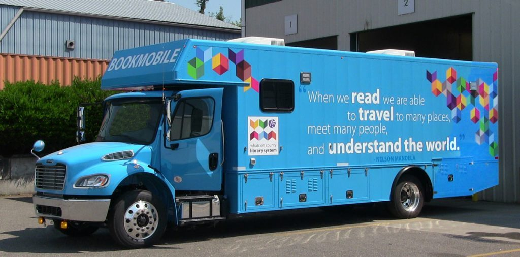 """Bookmobile side view with quote """"When we read we are able to travel to many placees, meet many people, and understand the world."""" Nelson Mandela"""