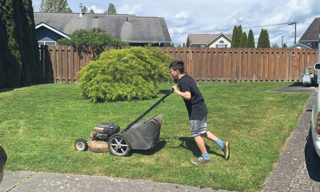 photo of boy mowing lawn