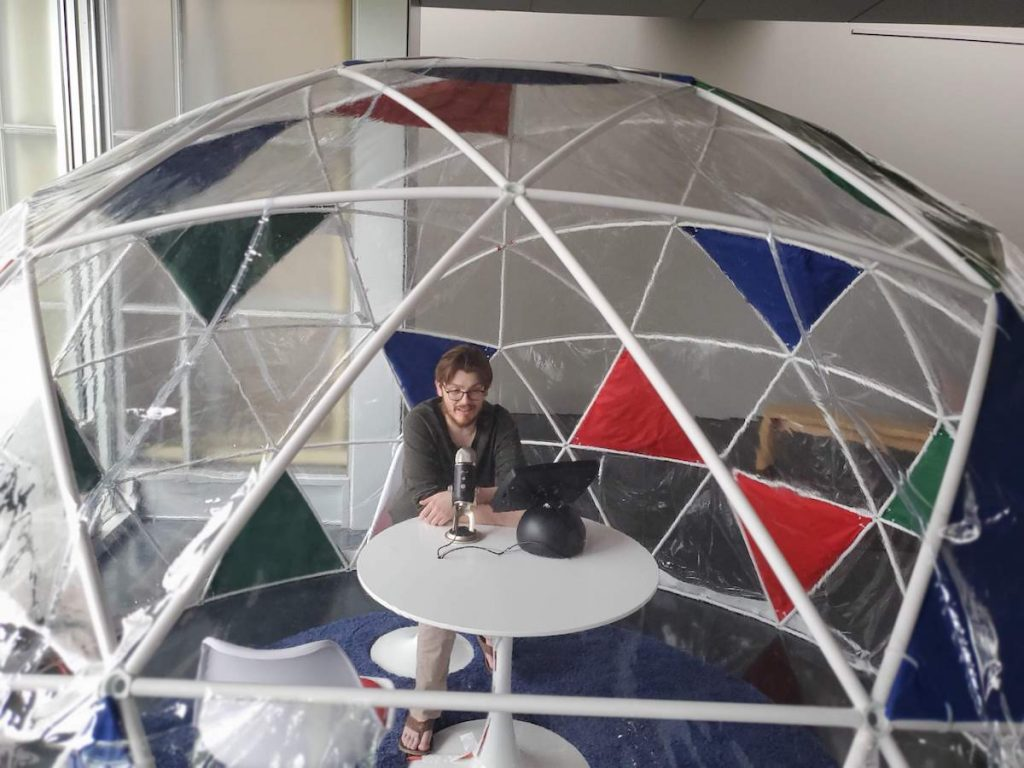 man speaking into microphone in geodesic dome