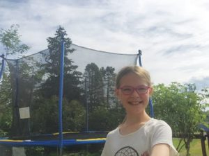 young girl with glasses in front of trampoline