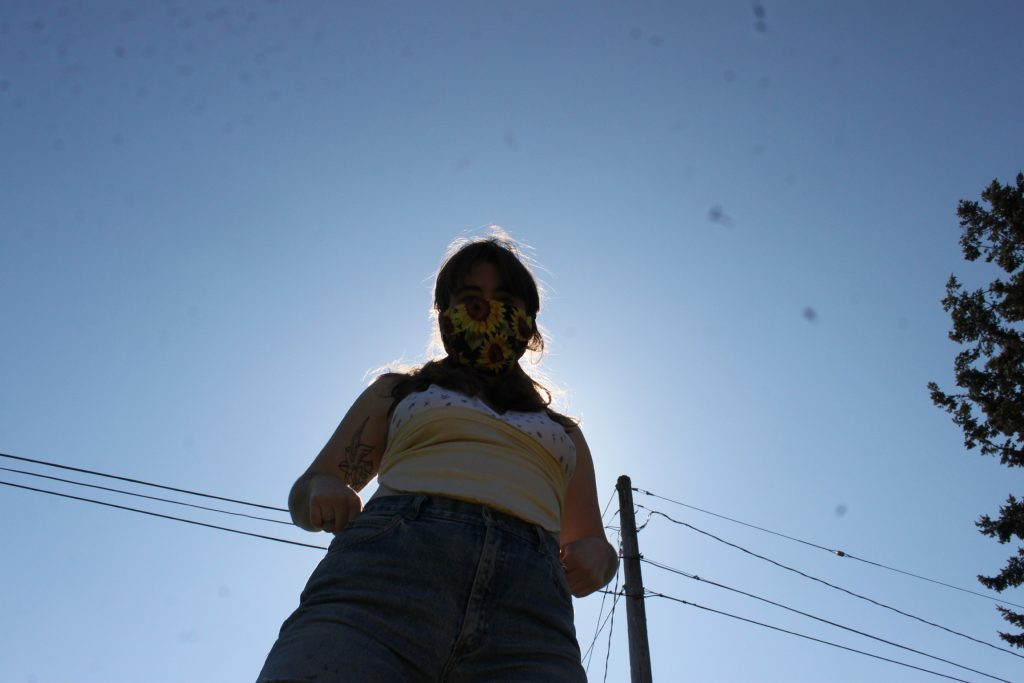 image of woman wearing facemask with sun in background