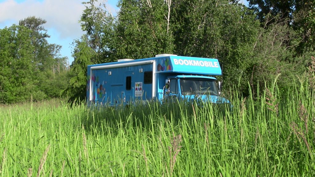 Photo of bookmobile in tall grass