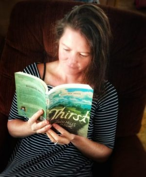 "Photo of author Heather Anderson reading her book, ""Thirst: 2600 Miles to Home"""