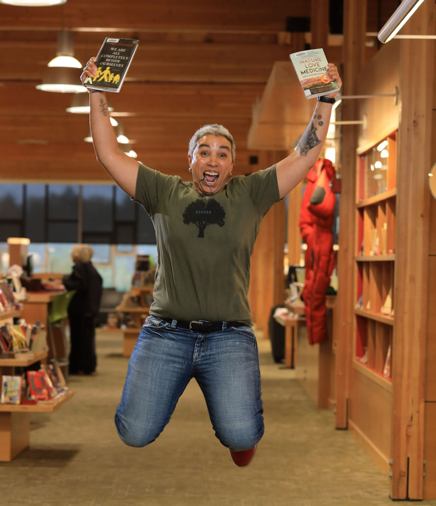 Woman jumping in library holding books