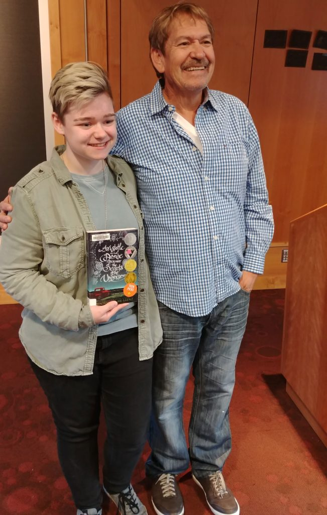 Photo of two people, one holding a book