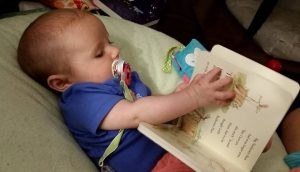 Photo of baby holding a book